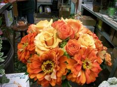 Bouquet in the making - so vibrant!  2 shades of orange roses, with summery zinnias.