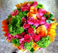 Bright prom bouquet with green viburnum, orange roses, oranger gerbers, hot pink spray roses and green athos poms by Always With Flowers - Lemont, IL