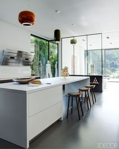 Brussels Home - polished resin floor, island by Bulthaup, vent hood by AEG, stools by E15, fixtures by Ionna Vautrin