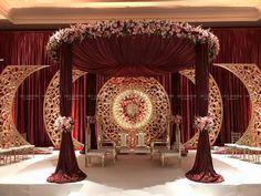 Garnet and floral mandap with golden medallion backdrop - Moyiki Sites Wedding Backdrop Design, Desi Wedding Decor, Wedding Hall Decorations, Indian Wedding Receptions, Wedding Stage Design, Luxury Wedding Decor, Wedding Reception Backdrop, Marriage Decoration, Wedding Mandap