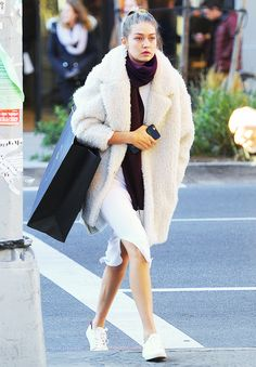 Gigi Hadid wears a white dress with a burgundy scarf, shearling coat, and white sneakers