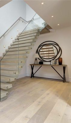 This contemporary entrance hallway features a stylish twist effect mirror featured on an industrial living style console table complete with tripod lamp