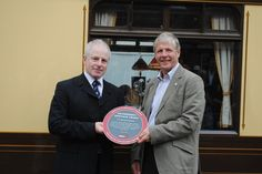 Bluebell Railway, August 2010. Institution President Keith Millard (right) presenting the award to Roy Watts from the Bluebell Railway.  The day had 108 members attend a special pullman lunch train in honour of the award.