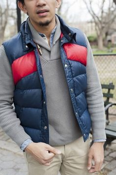 The versatility of a dark blue gilet and beige chinos makes them investment-worthy pieces.   Shop this look on Lookastic: https://lookastic.com/men/looks/navy-gilet-grey-shawl-neck-sweater-light-blue-long-sleeve-shirt/15874   — Light Blue Chambray Long Sleeve Shirt  — Grey Shawl Neck Sweater  — Navy Gilet  — Beige Chinos