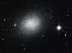 """NASA's Hubble Space Telescope took this picture of UGC 5497, a dwarf galaxy in the constellation Ursa Major, some 12 million light years away. The galaxy is full of newly formed bright, blue stars, which lend the galaxy a blue tint. Eventually they will explode as supernovae. NASA says that in the picture the galaxy """"looks a bit like salt sprinkled on black velvet,"""" and we agree."""