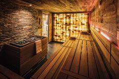 Stimmungsvolle Designsauna mit Natursteinwand und hinterleuchteter Salzsteinwand im Fairmont Hotel Vier Jahreszeiten. Die Innenverkleidung aus Altholz sorgt für den ganz besonderen Charme.