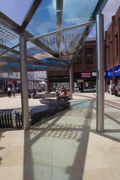 Llanelli town centre glass canopy, 2013. Carbon fibre threads, folded copper mesh, and folded stainless steel mesh pieces laminated in toughened glass, alongside vinyl coloured glass panels in gradating shades of blue. Photo by Dan Staveley.