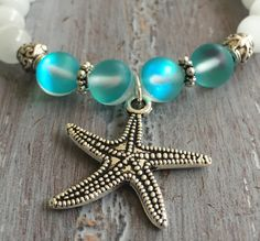 Starfish Bracelet with White Cat Eye Gemstones with Crystal Aqua Blue Beads. STARFISH BRACELET -8mm Natural White Cat Eye Gemstones. - Four Beads that are 8mm Glowing Crystal Aqua Blue. One side of the bead is light aqua color & the other side is darker aqua blue. No special light is