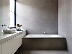 Low maintenance built in bath with complimenting bespoke vanity bench ,large grey tile. Lubelso Bathroom