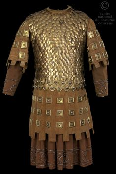 Comedy-French N °: D-CF-739 B ROLE: Peer Knight COSTUME DESCRIPTION: Skin armor doublet lined with metal plates and copper scales on a tunic and skirt in brown wool. FRONT