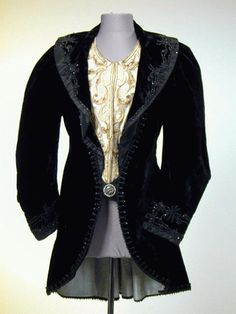 Victorian Black Velvet Jacket  Probably French, 1890s   Cut away style, with wide round collar, integral ivory silk vestee with scrollwork embroidery, the coat trimed at edges with black jet beadwork, singular decorative buttons at front and back, blue figured silk lining