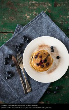 gluten free pancakes with blueberries and marple syrup on blue linen and wood table