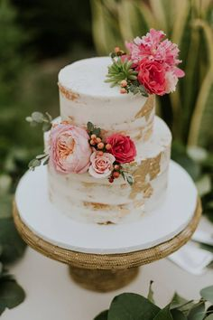 Pretty white wedding cake with gold accents adorned with pink spring flowers