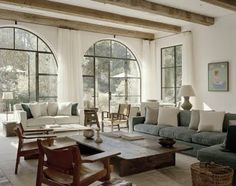A set of Spanish Chairs look amazing in front of these large, iron, curved windows.