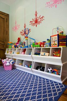 Playroom design with blue lattice rug, green gray walls paint color, red & pink chandelier wall stickers, pink polka dot baskets and white stacked open storage bins, playroom.