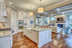 Traditional Kitchen with stone fireplace, Pendant Light, Box ceiling, Crown molding, Hardwood floors, Ceiling fan, Columns