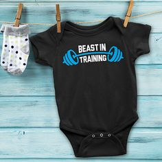 """The world will know how tough you and your kids are when they sport these new """"Beast In Training"""" #BabyOnesie. They match your """"World's Strongest Dad"""" Shirt perfectly. Everyone will know not to mess with this team. You will be one intimidating crew when you all walk into the the CrossFit gym together. Choose from black, navy, brown and few other options. Use coupon code PINFIVE for 5% off! #giftideasfinder #newbabygift #beastintraining #babyshowerideas"""
