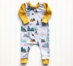 Adventure does await with this original Mami's Little Muse baby boy romper! It features a wonderful print in a mix of mustard yellow, blue, teal, and grey looming mountains, with coordinating mustard sleeves, neck trim and ankle cuffs. The romper is handmade with an keen eye for detail using a high quality, stretchy polyester blend spandex so it easily pulls up over baby's body through the neck hole. There are no snaps between the legs (because we all know how snaps can bust open), but I can…