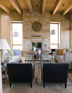 An antique wagon wheel hangs on the Aspenbark stone fireplace. The custom sofa and chaise are covered in Granada Natural, an artist's canvas linen from Framing Fabrics. Black leather Benjamin chairs are by Oly; Tolomeo Mega floor lamps by Artemide; hair-on-hide rug, ABC Carpet & Home. The coffee table and side table were made by Sparky's Metalworks.