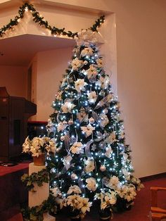 """Christmas Tree ~ Various white, clear, iridescent, and silver ornaments with large white poinsettias and various silver & white ribbon or white tulle to accent the tree and for the tree topper bow. The LED white lights provide a better ambiance of an """"ice effect"""" than regular clear mini lights"""