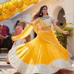 You can be assured to make a great style statement with this yellow satin banglori, gota satin lehenga. This lehenga is enhanced with zari embroidery work .Buy this latest designer lehenga choli online .Paired with matching choli and net dupatta. Bridal Lehenga Choli, Indian Lehenga, Rajasthani Lehenga, Choli Dress, Yellow Lehenga, Red Lehenga, Anarkali Gown, Indian Wedding Outfits, Bridal Outfits