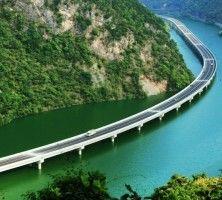Уникальный мост в Китае вдоль реки  Авиабилеты Москва - Бангкок от 24000 руб.  В провинции Хубэй в Китае пустили в эксплуатацию новый уникальный мост который проходит над рекой но не пересекает ее. Четыре километра дороги построили по руслу реки.   Сделано это вовсе не для красоты а для сохранения деревьев в гористой местности через которую нужно было провести эстакаду чтобы соединить два района. Мост назван Экологическое шоссе.  Новости туризма  Усиление мер безопасности на улице разврата…