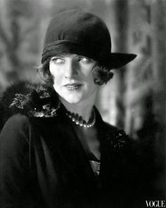 Actress-dancer Leonora Hughes in 1923 portrait, wearing dark cloche with brim jutting out on one side, pearls, and fur over shoulder.