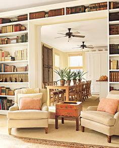 Love this:  Wide doorway opens to kitchen; custom bookshelves; armchairs in chenille; chinese tea box used as table; kitchen: door from Morocco against wall; chair seats covered in different fabric