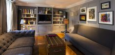 The snug - woodblock floor, antique chest, wool-covered sofas and grey painted panelling
