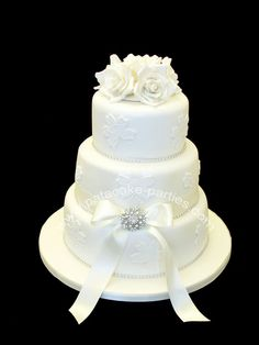 White on white wedding cake: lace applique pieces; white sugar roses; ribbon; bow; and diamante brooch -and finished with a generous spray of pearl lustre.