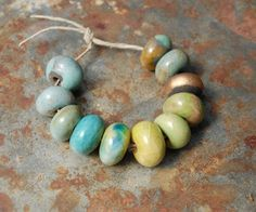 Handmade and desgined with love, these beads are happy to be just as they are but would also love your creative input. Add sparkling gemstones or rustic seed beads... Perfect for a necklace or ornament. Joy, Love, Peace! For the set shown...  Beads from: 10 mm x 14 mm Gaea handmade ceramics are fired to almost 2200 degrees to make them beautiful and strong.