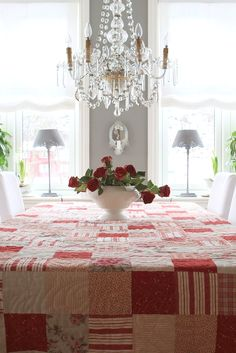 Lovely patchwork tablecloth...love the tablecloth, but would choose a different flower arrangement.