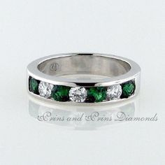 There are 3 = 0.39ct GH/VS – SI round cut diamonds and 4 = 0.61ct round cut tsavorite's channel set in an 18k white gold half eternity ring