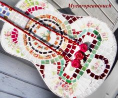 """This little guy started life as a guitar for a child. When I found it, it was tucked away in someones attic just longing to have new life breathed into it, as I do with all my recycled mosaic items. An up cycled, recycled piece of art. Many, many hours and weeks later I ended up with what I call """"Broken Songs and Melodies"""" mosaic guitar. This almost 31 inches long, formerly Acoustic Mosaic Guitar evolved from unusable to a decorative wall hanging for the visual enjoyment of the musi..."""