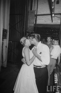 Rock singer Elvis Presley tenderly embracing & kissing the cheek of a female admirer backstage before his concert . Florida . August 1956 . Photo by Robert W. Kelley