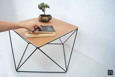 Mesa de Centro elemental. Utiliza como origen la geometría y las figuras básicas, mayormente modulaciones de triángulos estructurales con materiales como acero en color mate y madera de Okumé  $880.00