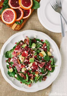Baby Spinach Salad with Blood Oranges recipe flavored with pomegranate seeds, avocados, feta cheese, thinly sliced red onions, and pecans.