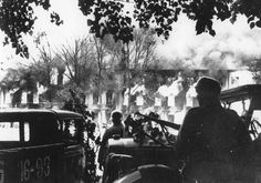 Operation Barbarossa: German soldiers watch a building burn in Smolensk, Russia during street fighting.
