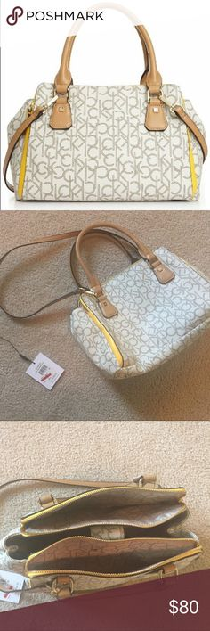 """Calvin Klein Hudson Monogram Satchel LIKE NEW Exterior features 2 zipper pockets; Interior features 1 zipper pocket 2 slip pockets; Snap closure; Gold-toned hardware.  Product Details  Size: One Size Color: Almond/Khaki/Canary Brand: Calvin Klein Model: H3JDJ1WT Dimensions: 8.50"""" h x 15.00"""" w x 7.00"""" l, 2.06 pounds Features  Exterior features 2 zipper pockets Interior features 1 zipper pocket 2 slip pockets Snap closure There is one unknown spot on the inside. It seems to come off with some…"""