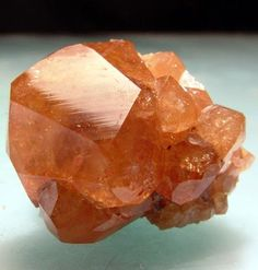 Grossular (Var: Hessonite), Ca3Al2(SiO4)3, Mana Mine, Barang-Turghao, Bajaur Agency, Federally Administered Tribal Areas, Pakistan. Largest crystal: 1.9cm. A bright and gemmy orange brown hessonite crystal dominates a matrix of smaller crystals, crystalline hessonite. Copyright: © TVM