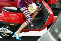 Silk striped capris, Chanel bag and turquoise pumps on a red Vespa in Milan.