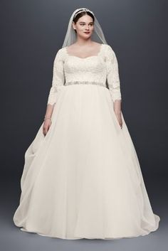 Made for the modern princess, this classic organza ball gown was designed with demure three-quarter lace sleeves and a flattering sweetheart neckline. The draping of the organza skirt adds the perfect