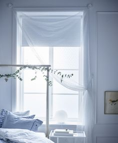A sheer white textile hangs as a curtain in a window. Curtain rod not necessary.