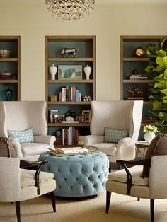 nice wing back chairs; like the multiple built in shelves and how they're all the same color, which is a darker version of the accessories in the room (pillows, ottoman); nice circular sitting area so everyone is involved, too: should remember this; those armchairs look comfy