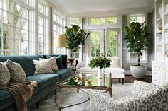A chic sunroom features walls clad in gray grasscloth lined with a peacock blue velvet of a adorned with leopard pillows facing a brass and glass coffee table and a barrel back leopard print chair atop a suede rug.