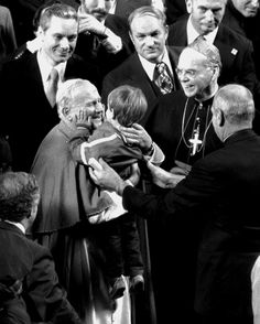 Pope John Paul II greets a young boy at Yankee Stadium while Cardinal Cooke smiles beside him.