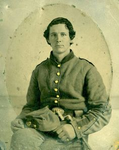 A tintype seated portrait photograph of an unidentified Wisconsin Civil War corporal. The image shows the soldier seated, holding his cap on his lap, and wearing the original gray uniform issued by the State of Wisconsin in 1861. Of interest is the fact that the soldier has his belt on upside down. The image could be of a soldier from the 4th, 5th, 6th, 7th, or 8th Wisconsin Infantry Regiment, as those units were issued the gray uniform in the picture.