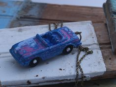 """A vintage metal toy car gets a cold enamel finish in different layers of color tones and is sealed with four coats of glaze. Rhinestone hubcaps finish off this fun statement piece. Comes on an 18"""" bronze chain. This is one of several models and colorways of cars that were in The Artisan Group swag bags for the 2015 Primetime Emmys."""