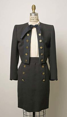 Wool suit and silk blouse (with jacket), by Yves Saint Laurent, French, 1986. Worn with large gold and black enamel earrings.