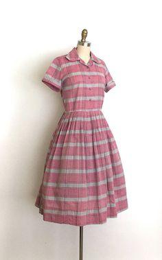 Classic 50s cotton shirtwaist dress. This dress features a great pink and grey plaid and the best square collar. Traditional shirtwaist silhouette, fitted bodice with short sleeves and turned up cuffs, nipped waist and a full pleated skirt. Button up front and side metal zipper.